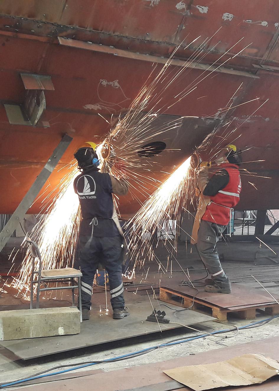 workmen-cut-into-the-hull-of-kando-at-ava-yachts